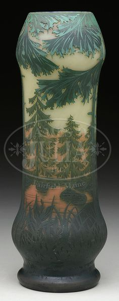 """DAUM SUNSET VASE. Daum vase has green cameo decoration of pine trees surrounding edge of pond. Pond has green ripple highlights against subtle orange water with orange rolling hills in background. All against frosted cream colored sky. Orange reflection on pond and hills gives feel of evening sunset. Signed on side in cameo """"Daum Nancy"""" with cross of Lorraine."""