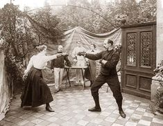You are viewing an important image of Duelling Fencers in April, 1904. It was taken in 1904.    The picture shows Man and woman duelling, 3 people watching.