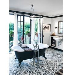 """As far as we can tell, the black-and-white bathroom isn't headed south out of style any time soon. If you love its classic good looks, but also yearn for a bit of boho, consider a tile floor that fits the palette, but rocks a pattern. We love encaustic tiles for their slightly rustic designs, and anything black-and-white by Ann Sacks. See more interior designers and floor tile and wood patterns on """" 12 Floor Ideas We Absolutely Love"""" on the One Kings Lane Style Guide!"""