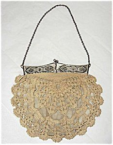 This lovely crocheted handbag dates to the late Victorian period, around the turn of the last century. The bag has a very unusual, beautiful silver frame with center clasp which forms four hinged panels and opens up into a square. Repeated on each of the four panels is a classic Arts and Crafts tooled or embossed design combining floral and geometric motifs