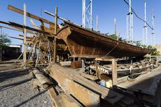 Timber scaffolding supports the hull during handmade construction of an ancient timber dhow. Sur, Ash Sharqiyah Region, Gulf of Oman, Sultanate of Oman.