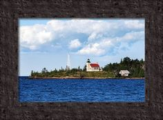 """Copper Harbor Lighthouse"" by Christina Rollo www.rollosphotos.com. Copper Harbor Lighthouse, Mohawk MI (Keweenaw Peninsula Lake Superior). Picturesque scenic view of the Copper Harbor Lighthouse with deep blue water on a partly cloudy day under beautiful blue skies, as seen across lake Superior MI, USA."