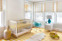 chambre bébé blanche et jaune décorée de fauteuil à bascule design et lampe bleus