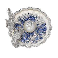 """Fountain Doves by Van Cleef and Arpels This pin """"Fountain Doves"""" is adorned with a pearl topped with a diamond. The two doves adorned with diamonds drinking water represented by a gradient of blue sapphires and diamonds. The interior of the fountain, is lined with small pearly round diamonds."""