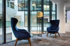 Office design for Taylor Wimpey, London by Morgan Lovell. These blue velvet hair-backed chairs create an elegant finish and perfect vista to look out of these floor to ceiling windows. Pendant lighting provides a focal point and improved visibility at the coffee table. For more workplace design inspiration and images from this project please click this image: