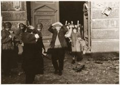 """Jewish families surrender to the SS during the suppression of the Warsaw ghetto uprising. The original German caption reads: """"Smoking out the Jews and bandits."""""""