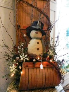 An old sled Christmas decoration with a snowman.