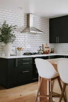 """Kitchen layout tips and designer advice - use """"The Kitchen Triangle"""" when planning a kitchen design for your fridge, sink, and oven. How to plan the placement of your major kitchen appliances. How to make your kitchen flow efficiently. Kitchen design ideas and inspiration. Black kitchen cabinets with white subway tile. 