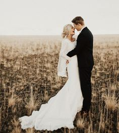 First look wedding photo of bride and groom in field. Bride wearing modest simple wedding gown with long sleeves and hair up