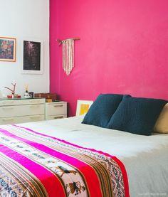 Quarto de casal com parede rosa e manta étnica.