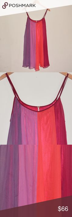 """Free People Small Rainbow Sorbet Trapeze Dress This is a Free People Rainbow Sorbet Dress. Size: Small. Color: Red/Purple/Orange. • Excellent used condition • Loose cut • Vertical stripe dress • Scoop neckline • Spaghetti shoulder straps • Layered chiffon outer • Wide stripes • Two-button cinch detail to the back of the waist • One loop end is undone. It is now attached to the button. See photo# 6 • Approx Measurements: Chest: 34"""". Length: 34"""". • Photos shown are both inside and outside of…"""