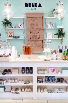 love this sweet shop, aqua wall color, open shelving and kraft paper sign