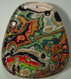Fordite Cabochon, aka Detroit Agate. Not an agate, just a happy accident! The original material was created many years ago at the Ford Rouge Plant outside Detroit, MI. Layer upon layer of paint overspray built up on metal racks that trans-ported new car bodies through the paint shop & into the oven, where each coat was baked hard: from the black & brown enamel of the late 1940s, to the colorful lacquers of the 1960s, to the vibrant base coats of the late 1980s