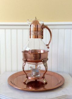 This is a beautiful ornate copper & glass carafe chafing set with matching ornate round tray. The set contains the glass & copper teapot with copper lid, Ornate copper stand, glass votive & candle for warming. Copper tray matches set & has a ornate etched scroll design. In very good ( barely used ) vintage condition! Great wedding decor, special occasion, barcart, or kitchen decor! Measures 14 height total, teapot 10 height x 5.5 diameter Stand 6.5 height x 5 diameter, Round T...