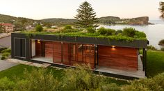 ArchiBlox has given this prefabricated beachfront house near Sydney a verdant plant-covered roof to help it blend into its clifftop setting.
