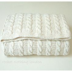 Rocket Clothing London by Linda Whaley. This cabled baby blanket is a beautiful blanket for a baby boy or baby girl as it looks special in any colour..... cream and neutral colours, fun brights, soft pretty colours or boyish blues, green and browns. These blankets shown are knitted in 100% cotton but they can be worked in any DK yarn.