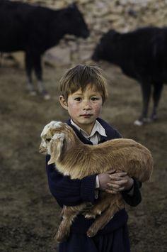 stevemccurrystudios: Young Hazara boy holds a baby goat in Bamiyan, Afghanistan.