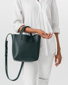 An effortlessly polished daily purse. Two handles and adjustable strap for over the shoulder or cross body carrying. Roomy interior zip pocket.