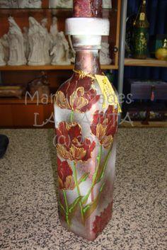 Botella de cristal con decoupage y filigranas doradas en relieve sobre fondo frost (hielo).