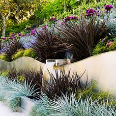 Making waves: Phormium 'Amazing Red,' silver puya, blue fescue, and threadleaf nandina add geometric contrast to the fluid movement of Baumann's wave wall. 'Ebb Tide' rose and catmint soften the overall look. Hillside Garden, Garden Shrubs, Sloping Garden, Landscaping With Rocks, Landscaping Plants, Hill Landscaping, Terraced Landscaping, Landscape Design, Garden Design