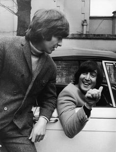 John Lennon of the Beatles gives a 'thumbs up' to bandmate George Harrison, after passing his driving test, February 16, 1965.