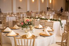 Reception with foliage garland on feasting table and lush, garden arrangement on round table