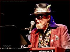 Dr. John if the voodoo ain't working just play. - Pinned by Mak Khalaf Legendary DR. JOHN visited Toronto Jazz Festival in 2013. He brought his beads feathers sculls and other voodoo paraphernalia on the stage. Whatever. Most people came for the music and were not disappointed. Versatile musician singing playing the piano red keyboard to go with his red suit and a guitar. He entertained the audience with his vast repertoire from early years to today. That's about 4 decades worth. With him…
