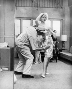 Orry-Kelly puts the finishing touches on a costume for Marilyn Monroe