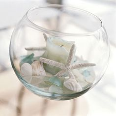 In a clear fishbowl, nestle a candle into a bed of pale sea glass and white shells. Its a great place to drop off treasures when you return from a walk on the beach, and it makes an instant centerpiece for entertaining on the fly. Experiment with scale when grouping your displayconsider size, color, and texture.