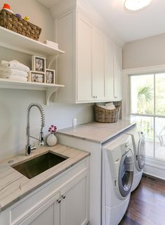 Laundry Room. Laundry room with white cabinets accented with nickel hardware and…