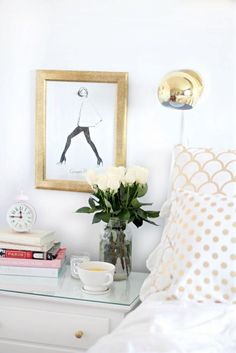 Bedside table detail with fresh flowers and framed Garance Dore illustration art print.