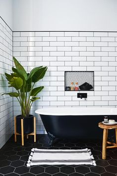 farmhouse-bathroom-monochrome-subway-tiles bathroom subway tiles claw foot tub plants color scheme