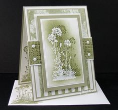 By Roxy (Rox71 at Splitcoaststampers). Stamp the image with colored ink. Stamp again in VersaMark & heat emboss with white powder. Sponge with ink color you used to stamp the first image. Add mats, designer paper, dry-embossed strip, brads.