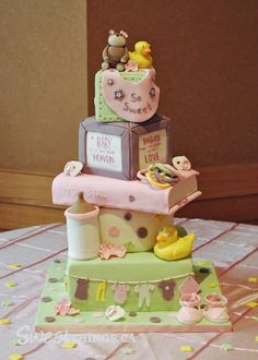 A baby shower cake in pastel colors.  Five tiers, bottom tier, a green square clothesline design, followed by a round tier with a duck and baby bottle.  The their tier is a pink book, followed by a building block, topped with a baby bib and animals.