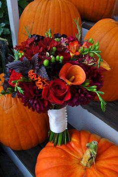 Red roses, burgundy dahlias, orange mini callas, and orange fresias for scent and a little bud texture.