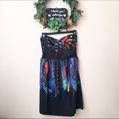 Bedded Tribal Roxy Stapless Cocktail Dress Cute dress adorned with turquoise colored beads. It has a black canvas with orange, red, light purple, blue, and turquoise decorated upon the dress. The dress is in excellent condition, but with thorough examination there is just an issue with the seam where the boning lays. The price had been dropped due to that flaw. The dress can fit a large or x-large frame.  Ask me any questions! Looking forward to having my dress find a new home! xoxo Roxy…