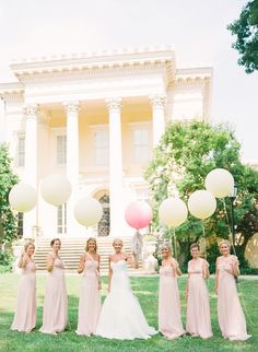 bridesmaids and bride with large color coordinated balloons