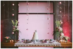 Obsessed with this cake table!!!  flower and crystal garlands, simple cake with personalized wooden figurine cake topper, vintage lace tablecloth, floral arrangements with soft pastel colors, and macarons in the wedding colors.  perfection!
