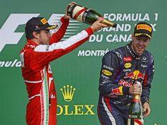 Der Verfolger duscht den WM-Führenden: Der Spanier Fernando Alonso (l) begießt Sebastian Vettel nach dessen Sieg beim Großen Preis von Kanada mit Champagner. (Foto: CJ Gunther/dpa)