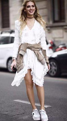 Chiara Ferragni usa vestido branco bordado, bomber jacket na cintura e tênis branco com solado mais alto.