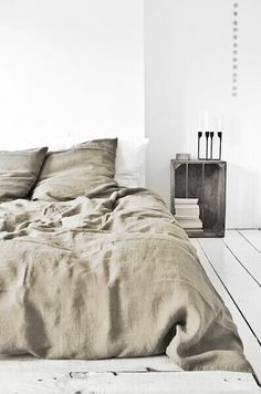 Bedroom white walls white flooring neutral linen raw wood cabinet candles simplistic minimalist