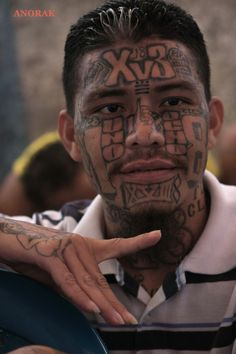 In this Sept. 1, 2012 photo, an inmate belonging to the Mara 18 gang gestures inside the prison in Cojutepeque, El Salvador.