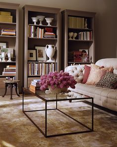 Neutral: Enhance the Ordinary  With a little doctoring, unfinished bookcases from a furniture store can take on a built-in look, and add architectural interest to a room. In this living room, three units were dressed up with crown molding and platform bases, then painted moleskin gray. Framed photos and bibelots form a library of objects that mingles with the books.