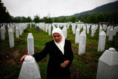May 17, 2012. Mejra Dzogaz touches the graves of two of her sons before the television broadcast of the court proceedings of former Bosnian Serb general Ratko Mladic's in Potocari, near Srebrenica, Bosnia and Herzegovina. She lost her husband, three sons and a grandson during the Srebrenica massacre in 1995.