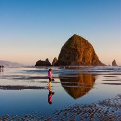 Photograph by @susanseubert // Haystack Rock is a 235 foot intertidal sea stack in Cannon Beach Oregon.  The monolithic rock is surrounded by tide pools home to many animals including starfish sea anemone crabs chitons limpets and sea slugs. The rock is also a nesting site for many sea birds including terns and puffins. Photographed #onassignement for @natgeotravel #oregon follow @susanseubert for more! by natgeotravel