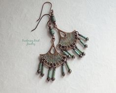 Bronzed copper fans with their rustic blue patina seem to have been just excavated in these boho-chic tribal chandelier earrings. The glass bead dangles are blue-green turquoise tubes and striped brown seed beads culminating in ball-tipped copper. ► just shy of 3 long ► fan dangle: 1