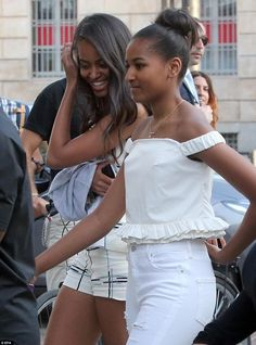 The Obamas arrived in Milan on Wednesday and were spotted shopping: Malia wore a matching black-and-white checked shorts and top combo (left) while younger sister Sasha wore an off-shoulder white top with flared edge and ripped white jeans (right)