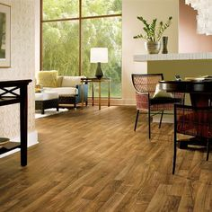 vinyl sheet flooring.  Looks like wood, warm underfoot, can be placed over concrete. About $1 sq ft.  Armstrong flooring has many options