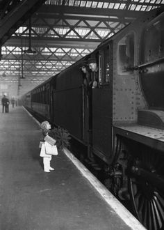 A little girl, laden with Christmas presents, engages two train drivers in conversation at Euston Station on December 22, 1936 (Photo by J. A. Hampton/Topical Press Agency/Getty Images)