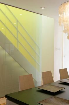 Frosted coloured glass panel next to a staircase. With light shining through illuminates the glass and adds colour to the room.